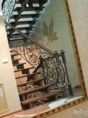 Металлическая лестница в черном цвете с кованым ограждением