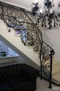 Белая лестница с черными перилами с коваными элементами
